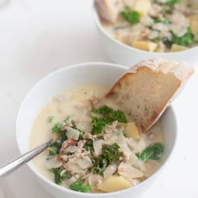 Two bowls of soup with spoons and pieces of bread dunked inside.