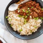 Gray bowl full of Vegan Red Beans and Rice with a spoon