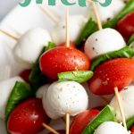Side angle shot of Caprese Sticks on a white plate, with a text overlay