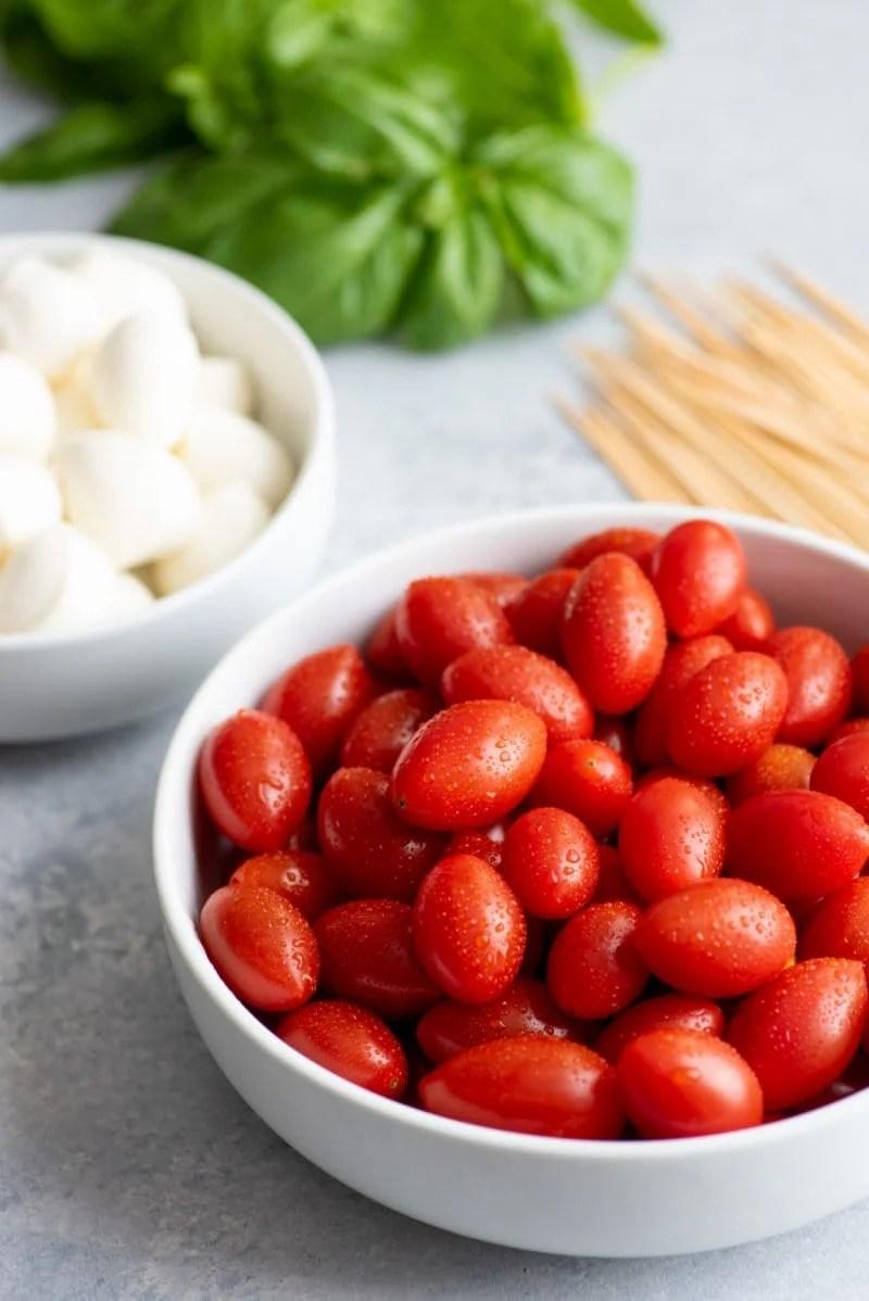 Side angle shot of Caprese Sticks ingredients - cherry tomatoes, mozzarella balls, basil, and toothpicks