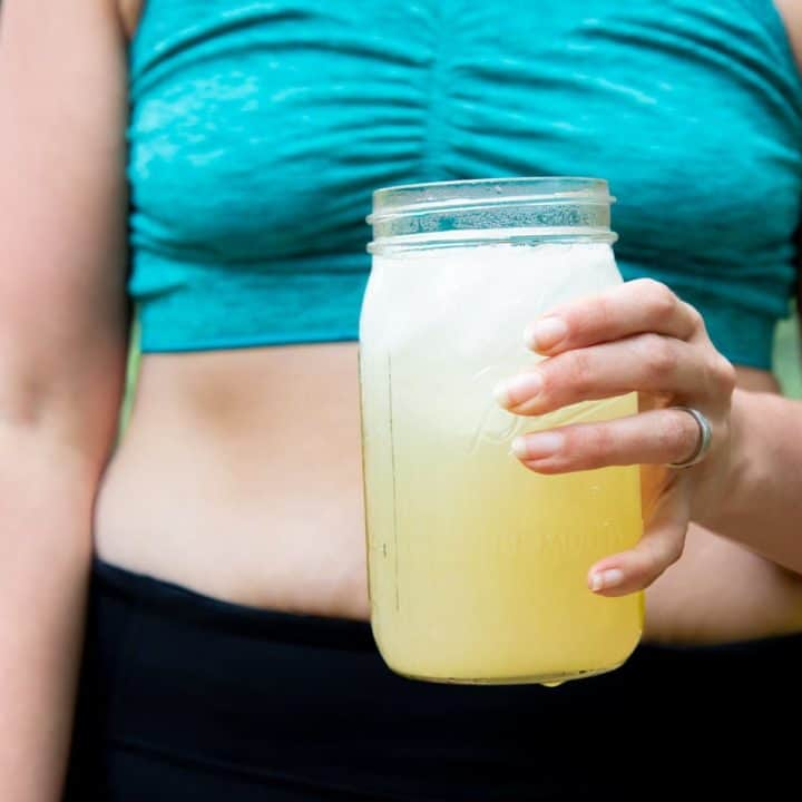Torso of a woman in a turquoise sports bra and black pants, holding a glass jar of Homemade All-Natural Electrolyte Drink