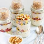 Side angle shot of prepared Meal Prep Fruit and Yogurt Parfaits in glass jars