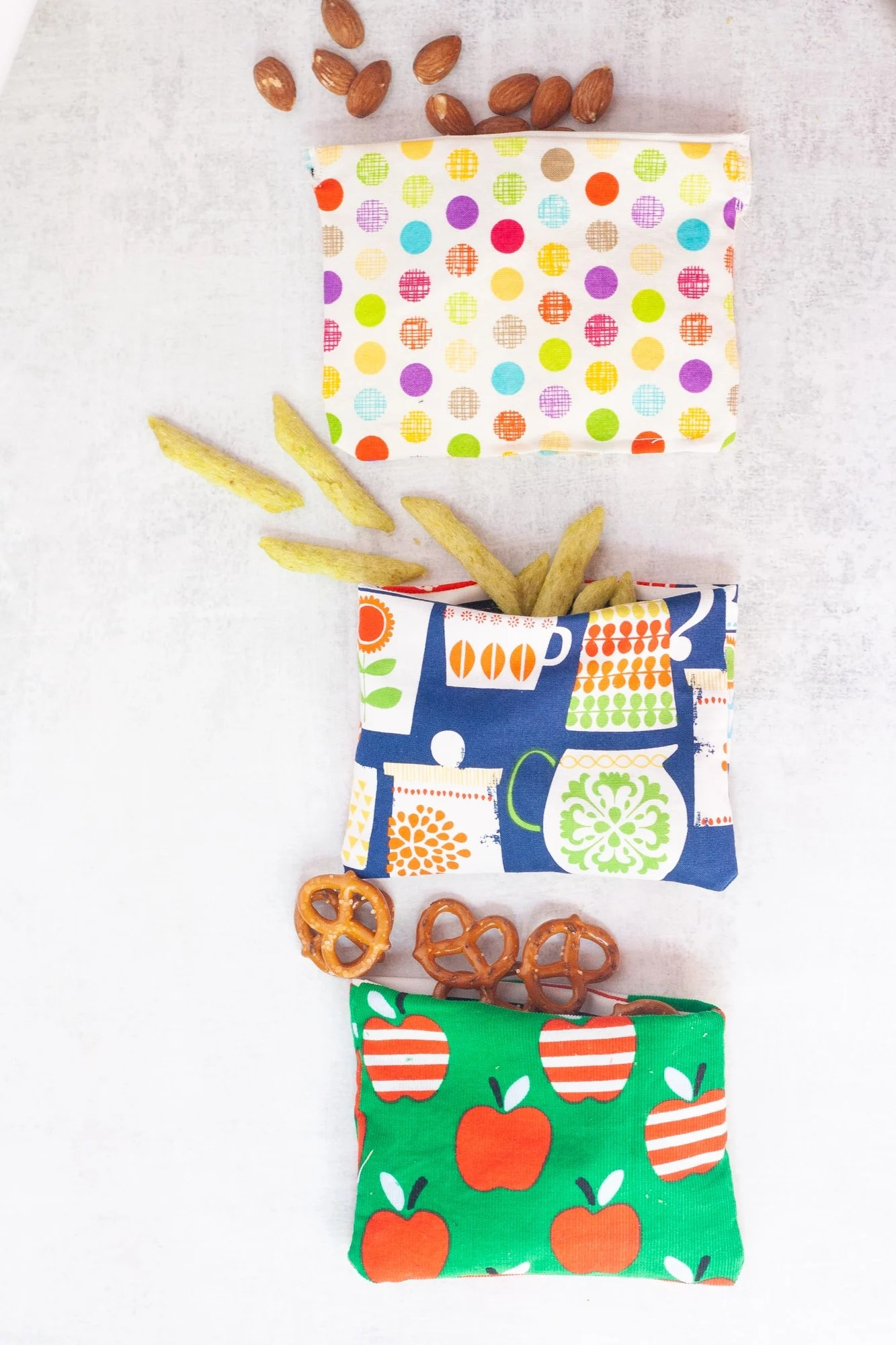 Three reusable snack bags lined up, each spilling out a different snack - pretzels, almonds, and crispy snap peas