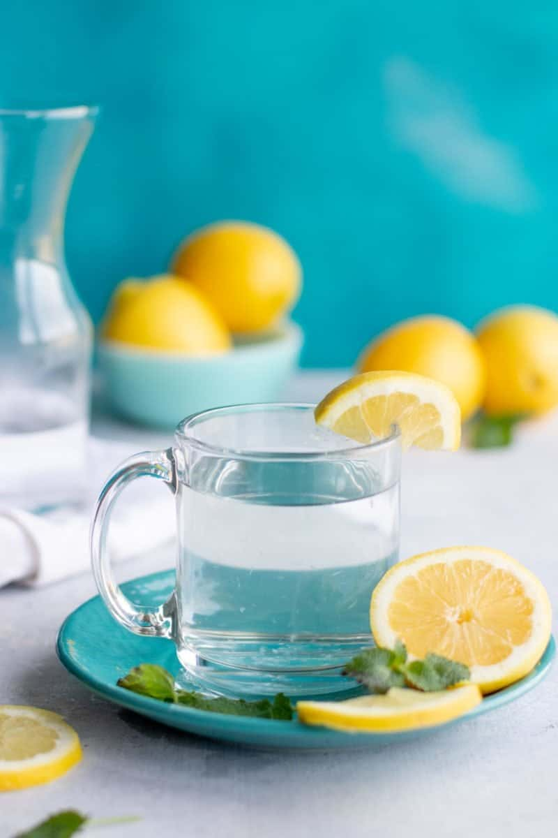 Side angle shot of a clear glass of lemon water on a blue plate, with more lemons and water in the background