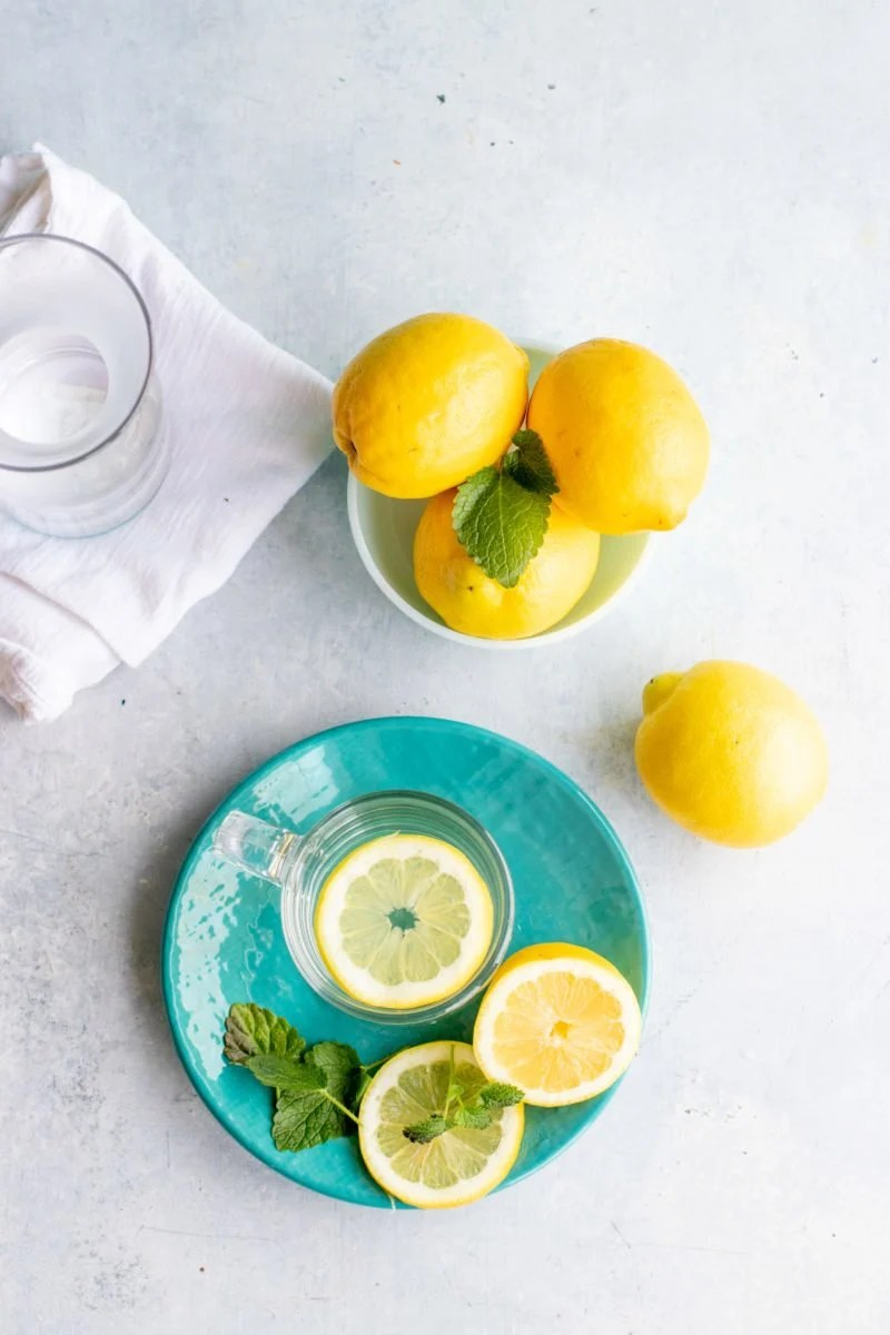 Overhead shot of a clear mug of lemon water on a blue plate, with a bowl of whole lemons nearby