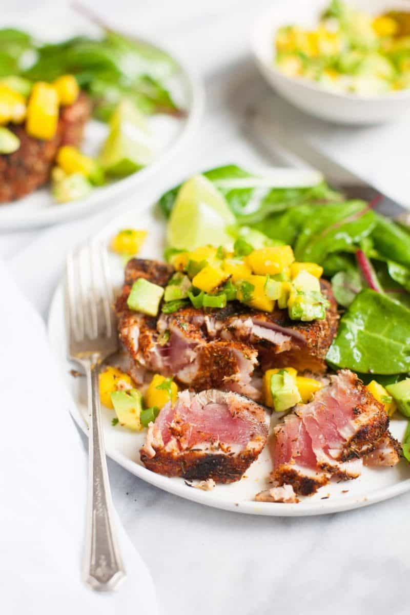 Blackened tuna steak topped with mango avocado salsa on a plate, cut to show the perfectly cooked pink interior.