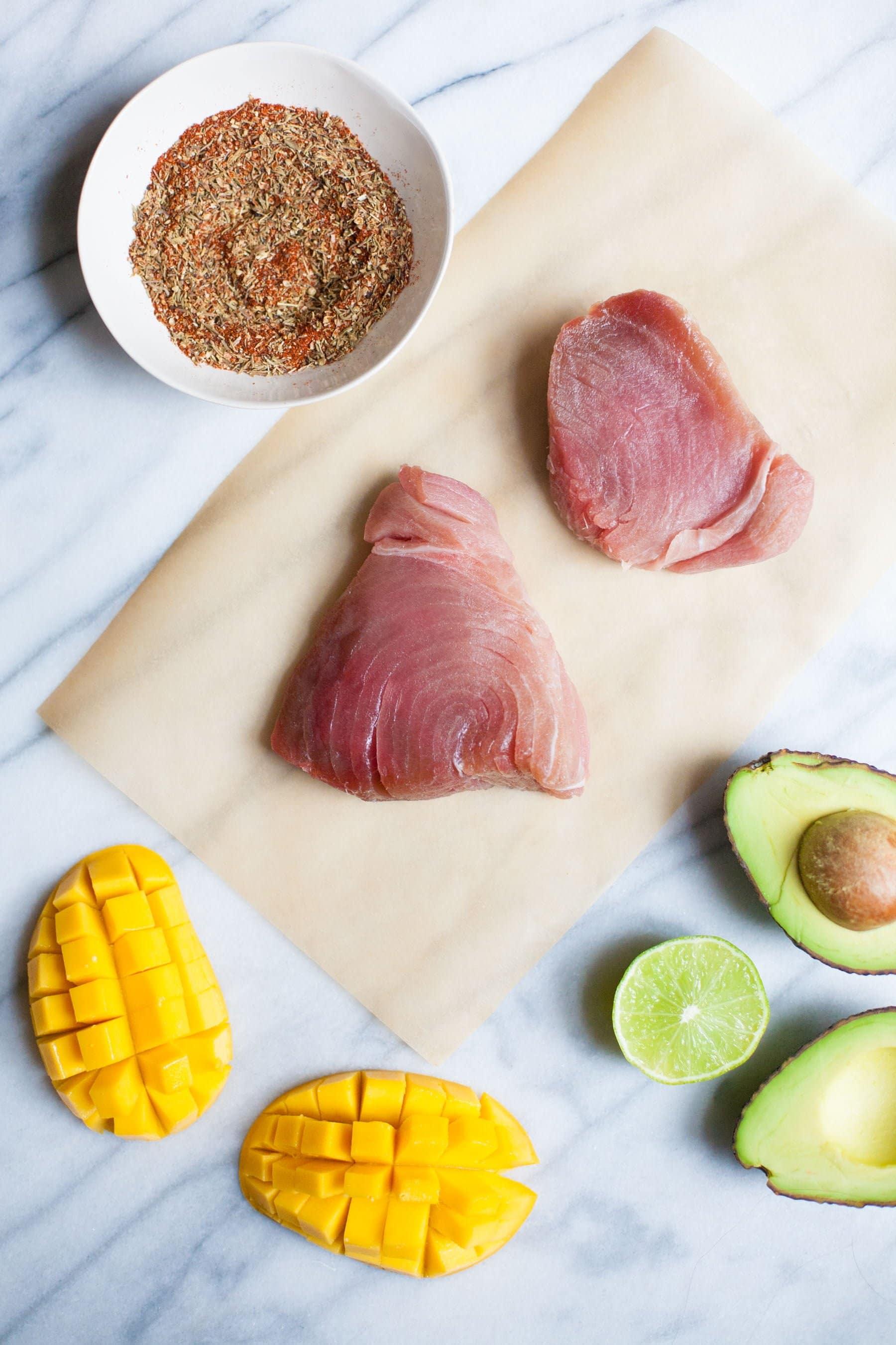 Overhead of two raw tuna steaks, fresh mango, avocado, and lime with a bowl of homemade blackening seasoning.