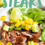 """Blackened tuna steak topped with mango avocado salsa on a plate, cut to show the perfectly cooked pink interior. A text overlay reads, """"Grilled Blackened Tuna Steaks with Mango Avocado Salsa."""""""