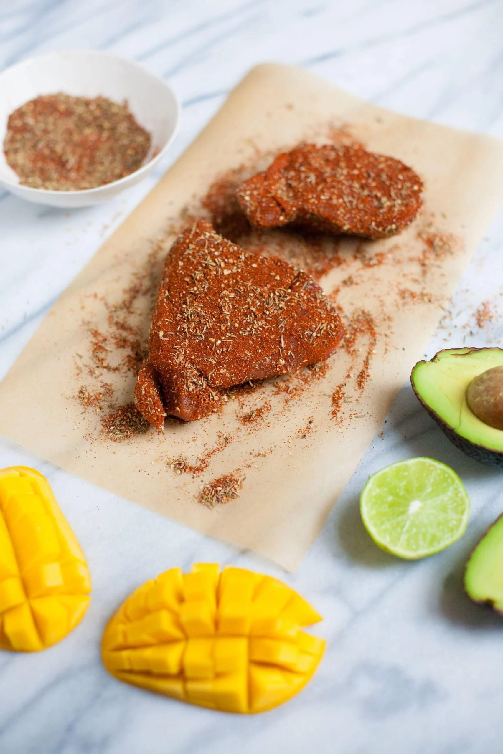 Two tuna steaks covered in homemade blackening seasoning sit on parchment paper with fresh mango halves and avocado halves nearby.