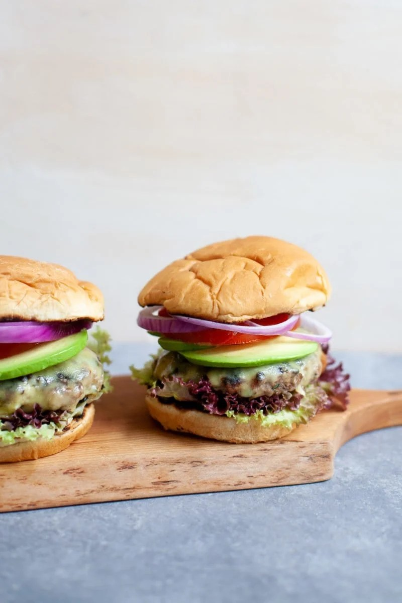 Two Garden Onion Burgers on a wooden cutting board