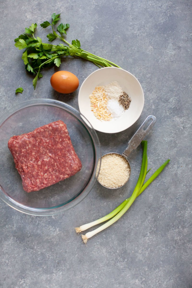 Overhead shot of ingredients for Garden Onion Burgers - beef, spices, egg, green onion, and breadcrumbs