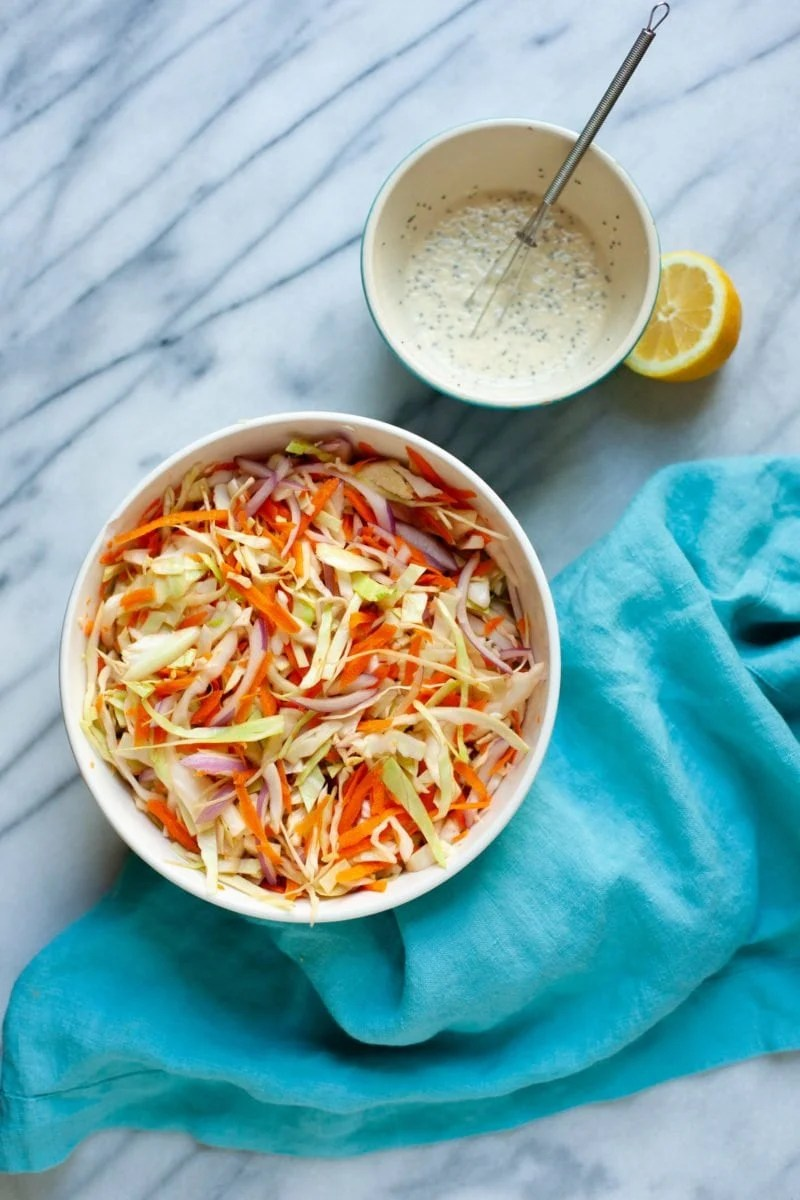 Overhead shot of dressing for Sweet and Creamy Coleslaw in a white bowl next to a bowl of shredded vegetables
