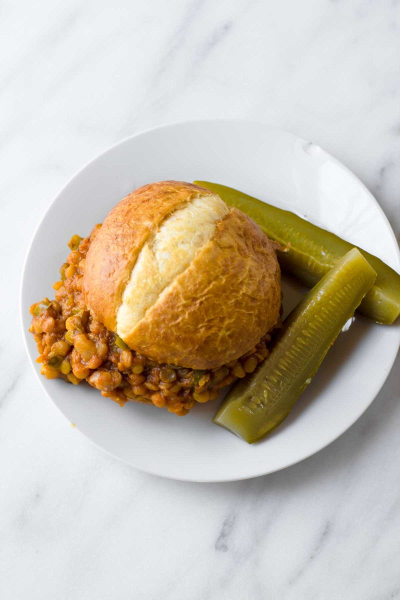 A Lentil Sloppy Joe sits on a white plate, with pickles off to the side