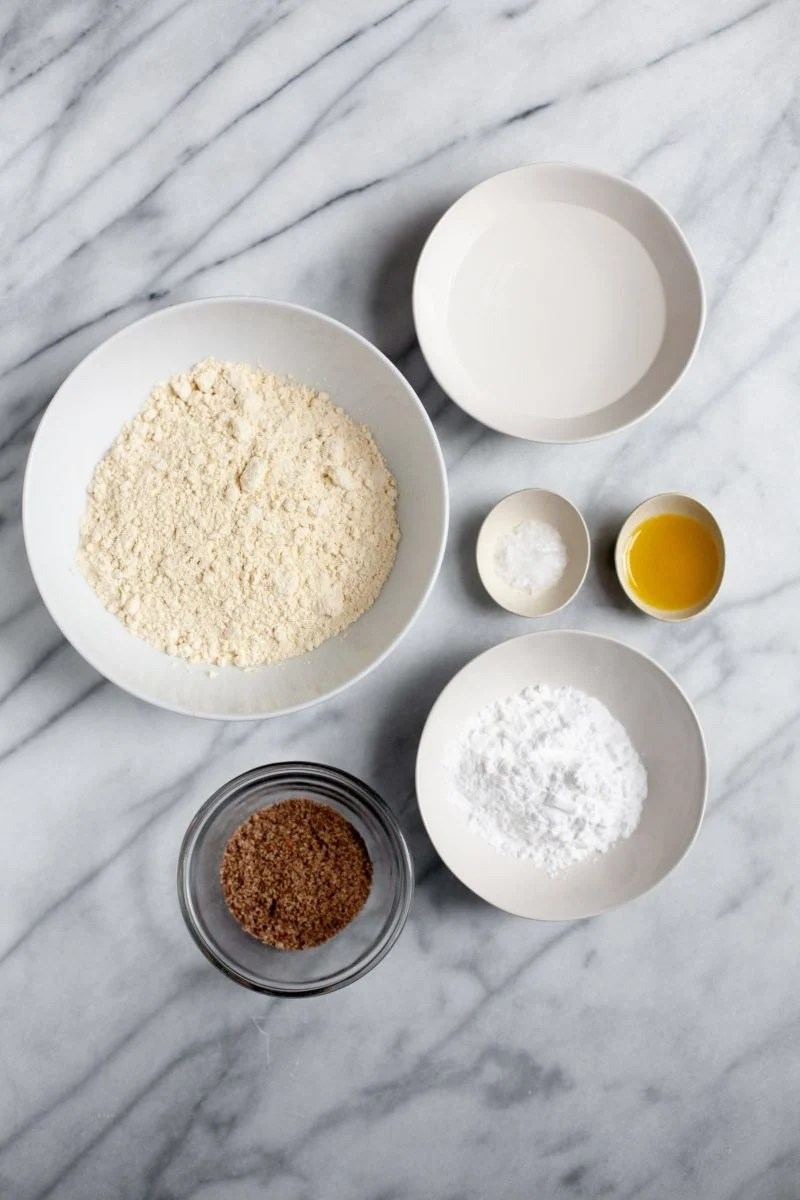 Overhead shot of ingredients for Gluten-Free and Vegan Chickpea and Flaxseed Homemade Pasta, with each ingredient in its own white bowl