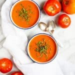 Overhead shot of Garden Fresh Tomato Soup on a white background, with whole tomatoes off to the side