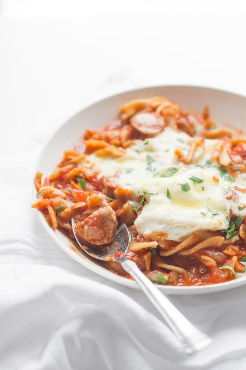 A spoon sits in a bowl of slow cooker lasagna soup.