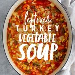 "Turkey Vegetable Soup in a stockpot on a marbled background. Text overlay reads ""Leftover Turkey Vegetable Soup."""