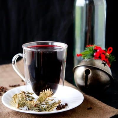 A mug of mulled wine wit steam rising from the top sits on a plate with pine branches and whole cloves.