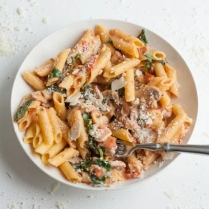 A bowl of Penne Rosa with shrimp and parmesan cheese.
