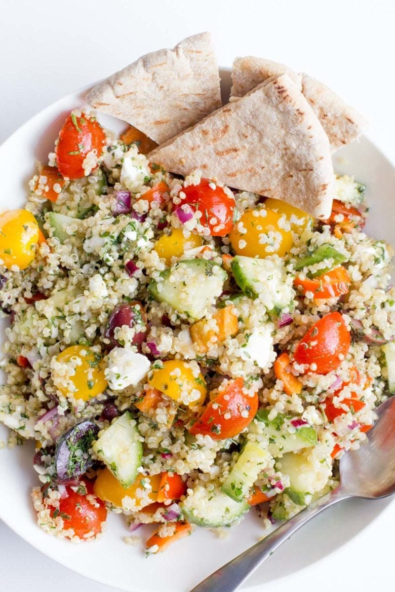 Greek Quinoa Salad in a white bowl, with triangles of pita bread on the side