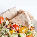 Greek Quinoa Salad in a white bowl with pita, with a text overlay