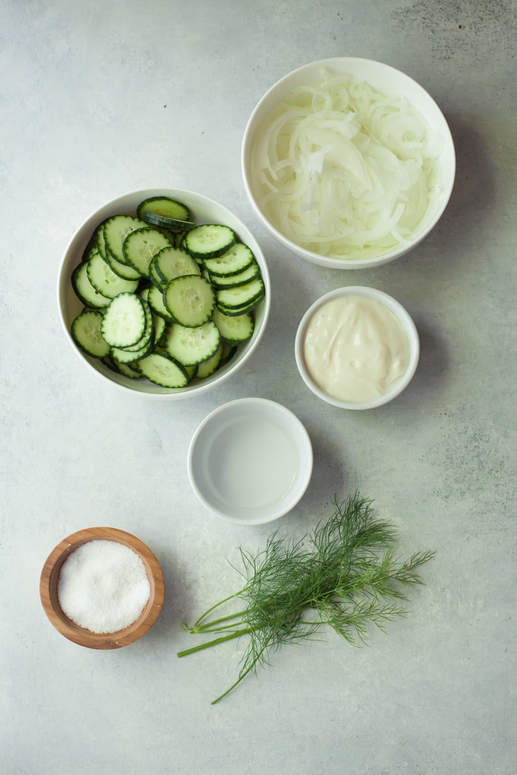 Overhead of six ingredients needed to make cucumber onion salad in bowls on a counter.