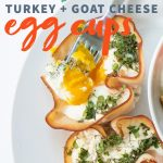 "Egg cups made of turkey and herbs sit on a white plate. Text overlay reads, ""Herbed turkey + goat cheese egg cups."""
