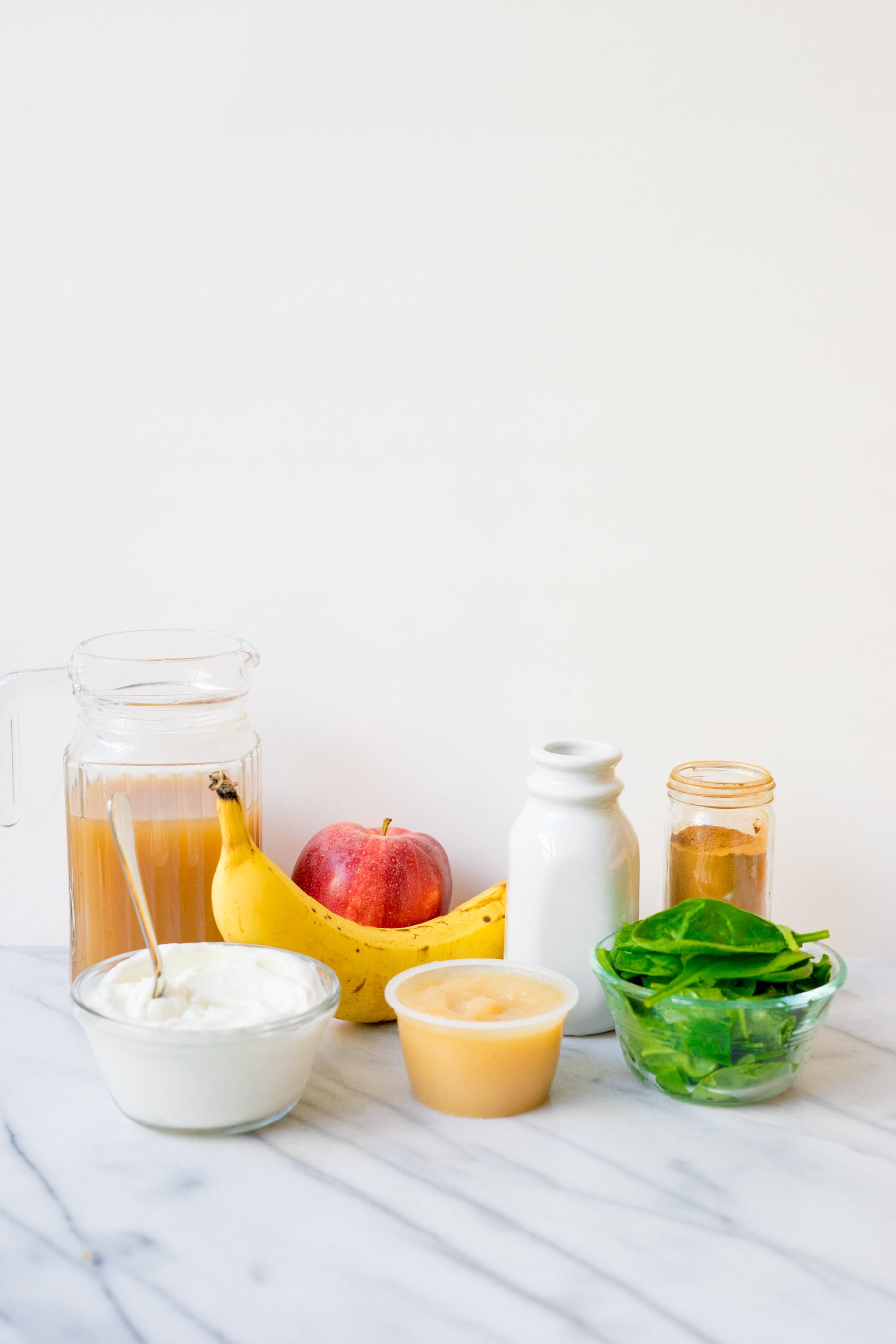 Apple cider, banana, milk, yogurt, spinach, applesauce, cinnamon arranged on kitchen counter