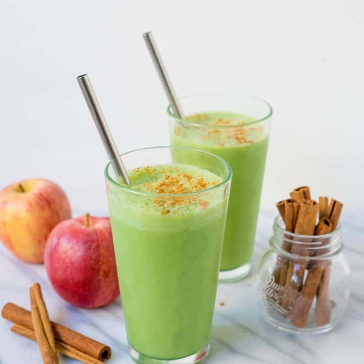 Two glasses of bright green smoothie with straws on white background with apples and cinnamon sticks garnish