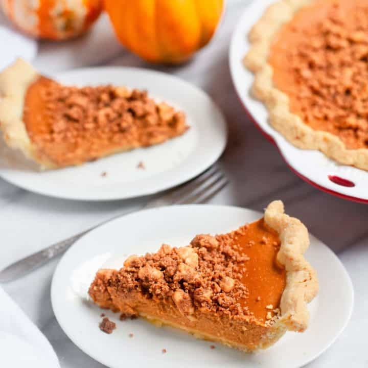 Slices of pumpkin pie with cinnamon walnut streusel on white plates