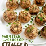 "Parmesan and Sausage Stuffed Mushrooms on a white plate. A text overlay reads ""Parmesan and Sausage Stuffed Mushrooms."""