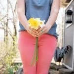 Shoulders-down shot of a woman in a blue shirt and pink pants, holding a bunch of daffodils