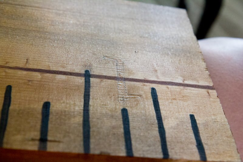 A numeral one outlined in pencil on a wooden growth chart.
