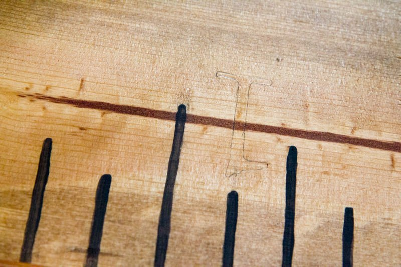 A numeral one outlined in pencil on a wooden growth chart ruler.