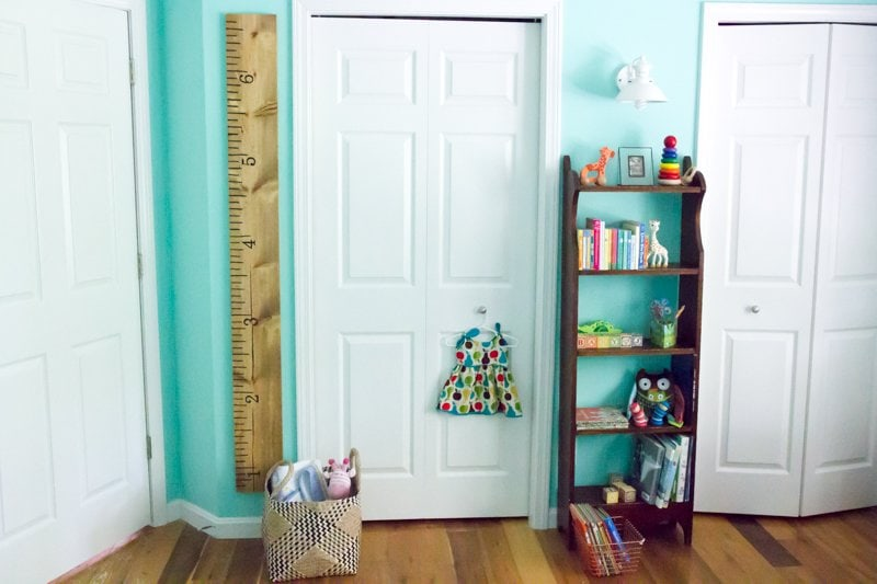 DIY Wooden Growth Chart Ruler hanging on a turquoise wall next to a white door in a nursery