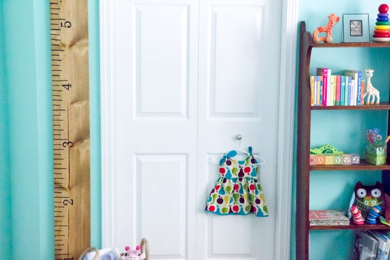 DIY Giant Growth Chart Ruler hanging on a turquoise wall next to a white door in a nursery.