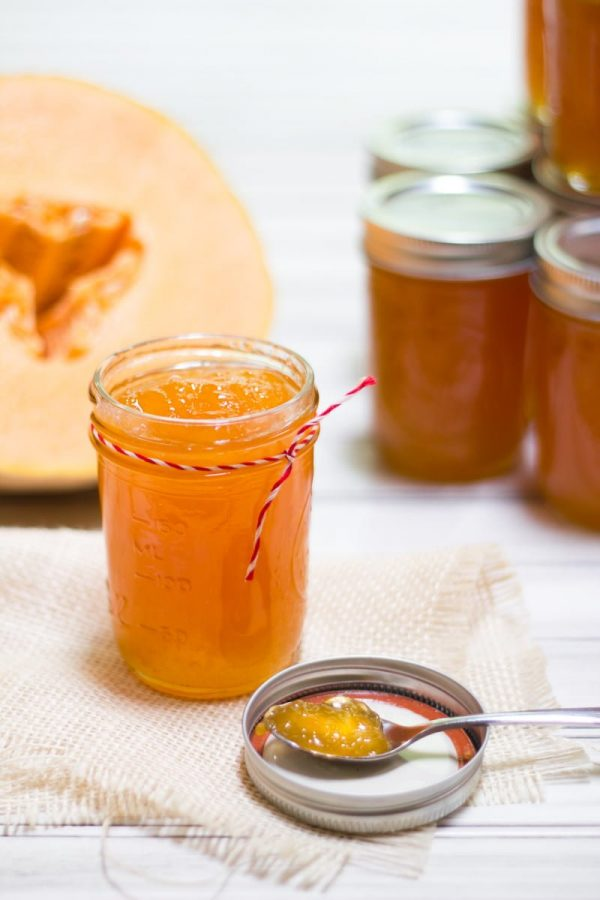 Open jar of Salted Cantaloupe Jam, with a halved cantaloupe behind