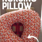 """An orange patterned nursing pillow rests against a brown chair. A text overlay reads """"How to Make a Nursing Pillow"""""""