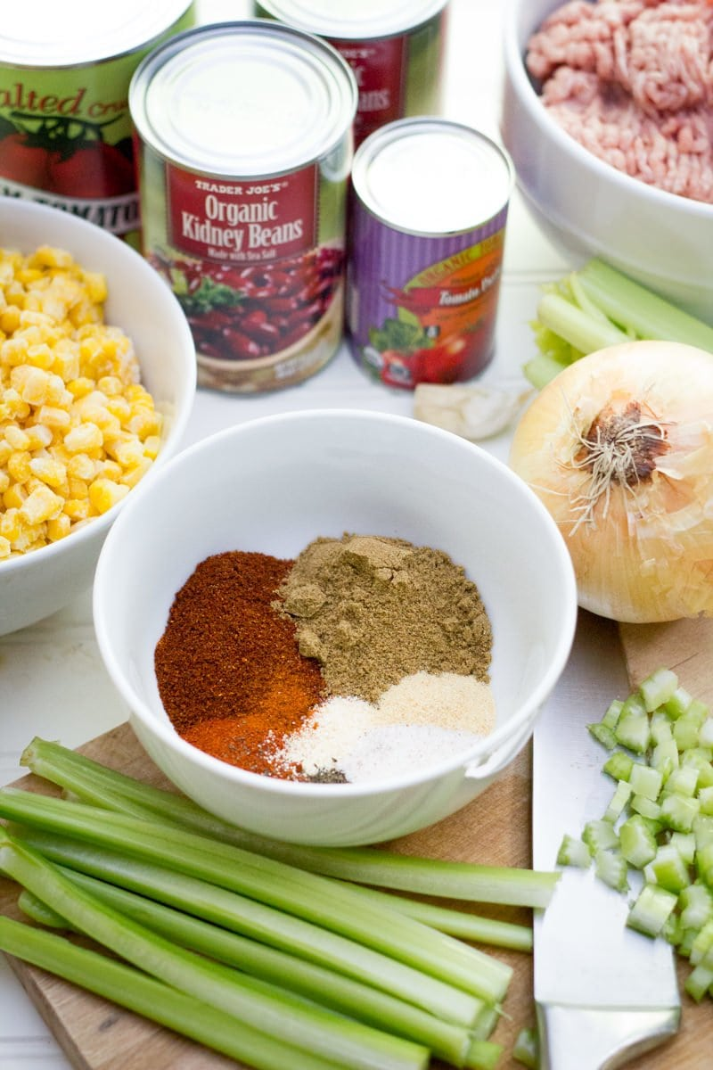 Ingredients to make taco chili sit together - cans of beans, corn, seasonings, celery, onions, and ground beef.