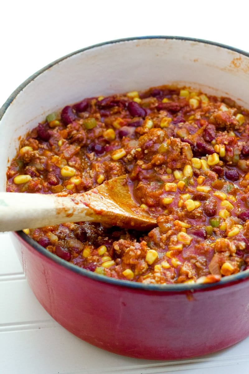 A wooden spoon mixes chili mixture together.