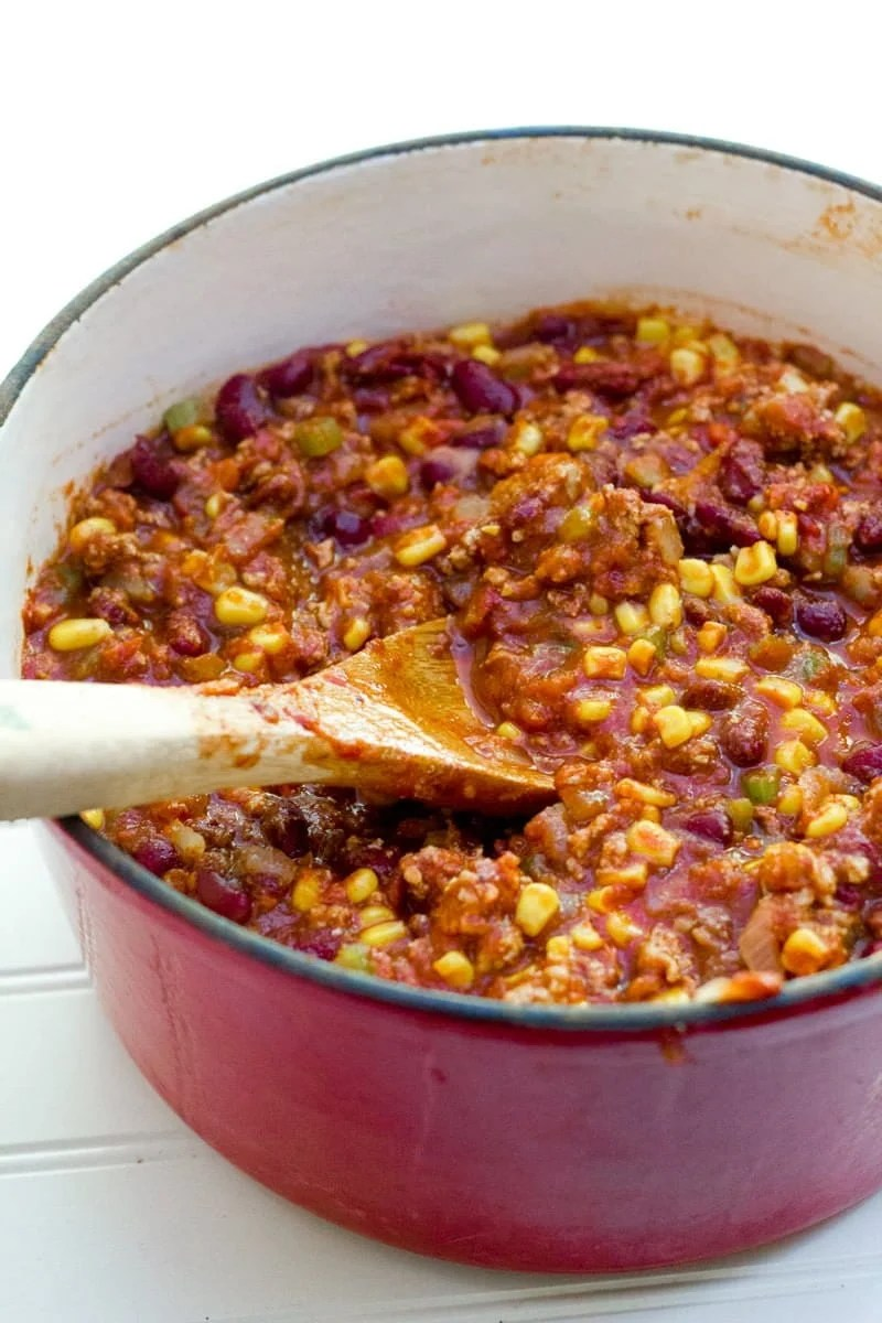 A wooden spoon mixes chili together.