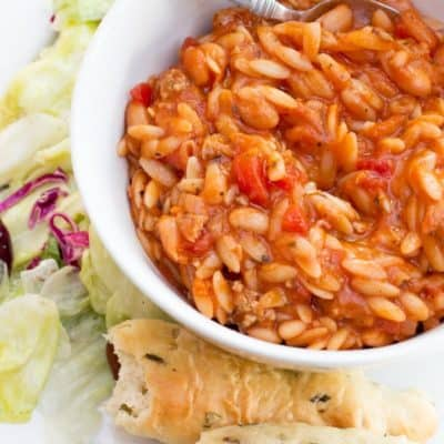 A bowl of Pasta e Fagioli sits on a white place, surrounded by lettuce and breadsticks.