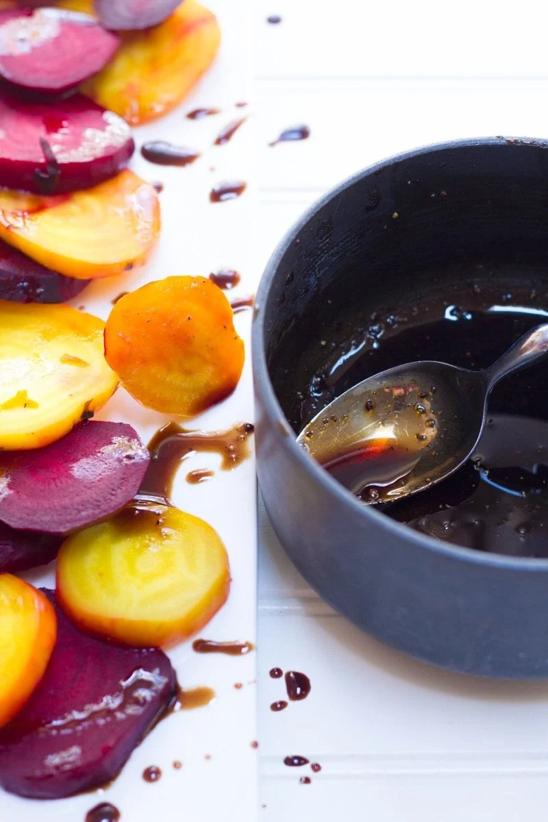 Roasted Beets sliced and arranged on a white platter, glazed with balsamic