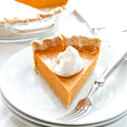 A finished slice of pie garnished with whipped cream sits on a stack of plates with a fork.