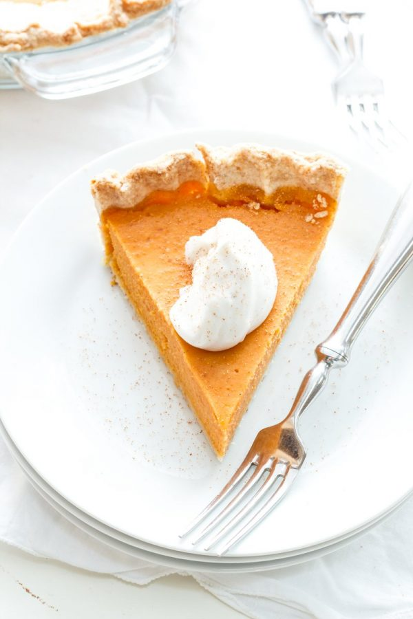 Overhead of a slice of sweet potato pie on a stack of plates with a fork.