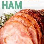 "Ham sits on a white dish. Juices from the glaze surrounds the ham. A text overlay reads ""Slow Cooker Honey Glazed Ham."""