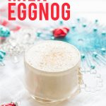 "Glass of Coconut Milk Eggnog surrounded by blue and red holiday decorations. A text overlay reads ""Coconut Milk Eggnog."""