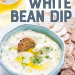"White bean dip drizzled with olive oil is in a light blue bowl, surrounded by crackers. A text overlay reads ""Roasted Garlic White Bean Dip."""