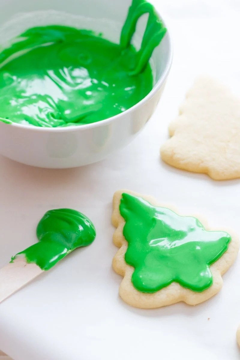 Cookies shaped like evergreen trees sit next to a bowl of green frosting. One cookie has some green icing on it already.