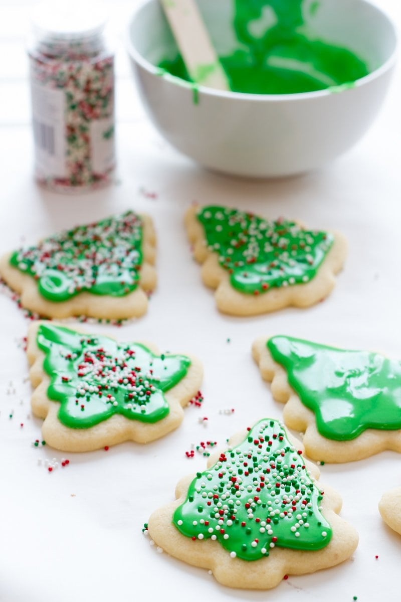Decorated Christmas tree sugar cookies with green frosting rest on a white background with a bowl of sugar cookie icing in the back.